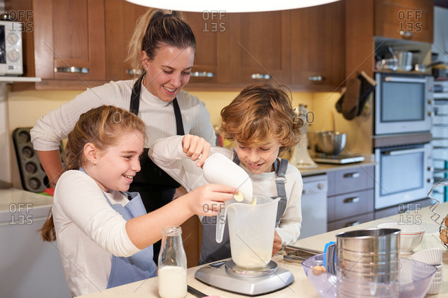 Stock photo of children with a woman wearing an apron in a kitchen preparing cupcake and putting the flour in a meter