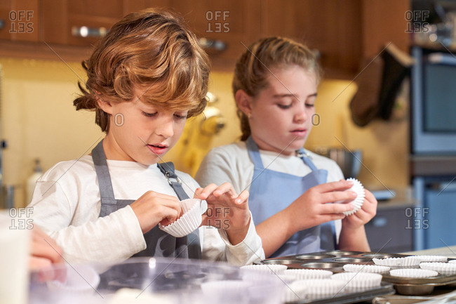 Stock photo of children wearing aprons in a kitchen peeling off pastry paper