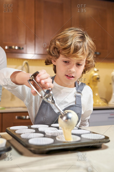 Vertical stock photo of a child with an apron emptying cream on plates ready to make cupcakes