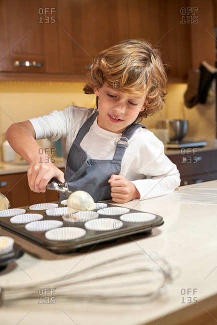 Stock vertical photo of a child pouring cream in silver prepared to make cupcakes