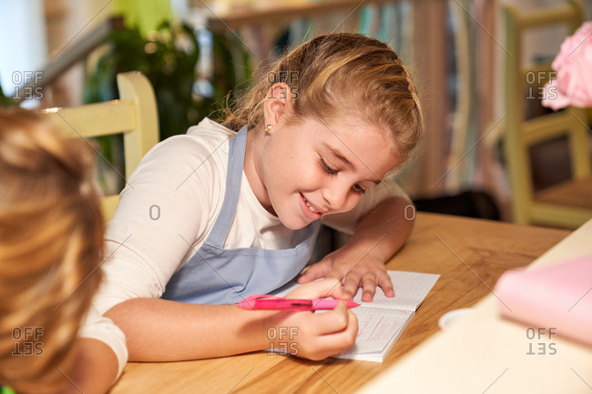 Stock photo of a girl sitting in front of a wooden table writing in a notebook and with a notebook and flowers in front of her