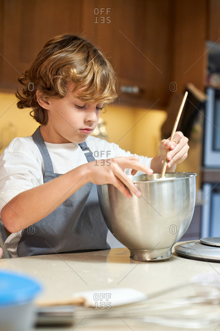 Stock vertical photo of a child mixing ingredients in a metal container