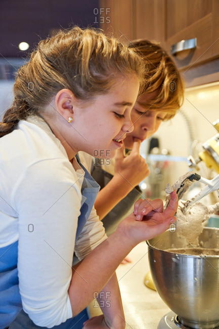 Stock vertical photo of two children testing with their finger the cream of a mixer