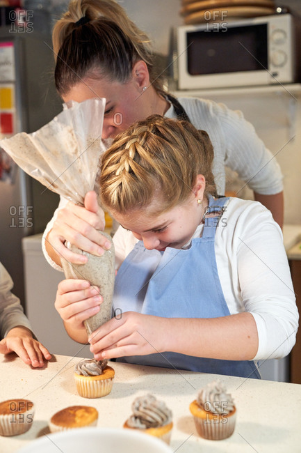 Stock vertical photo of a girl decorating cupcakes with cream with a pastry sleeve with the help of a woman