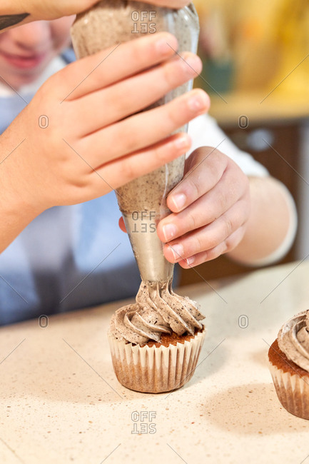 Stock vertical photo of the detail of the hand of a girl decorating cupcakes with cream with a pastry sleeve with the help of a woman