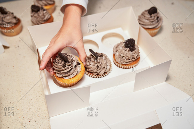 Stock photo of a detail of a hand putting a cupcake inside a white box