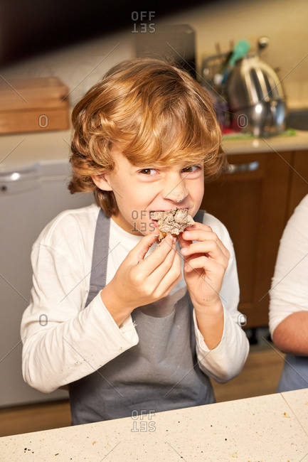 Stock vertical photo of a boy wearing apron eating a cupcake