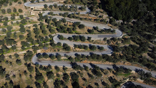 Top view of drone aerial view of snake road in the middle of a forest