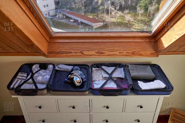 Ski goggles and hat placed in open luggage on top of drawer under window during winter vacation preparation at home