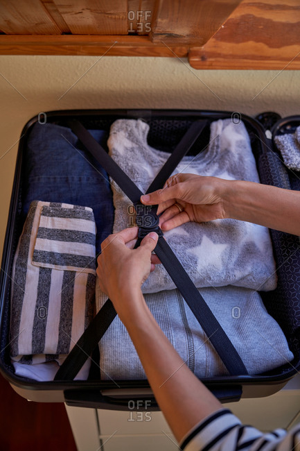 Anonymous lady in casual clothes putting garment into open luggage while preparing for trip at home