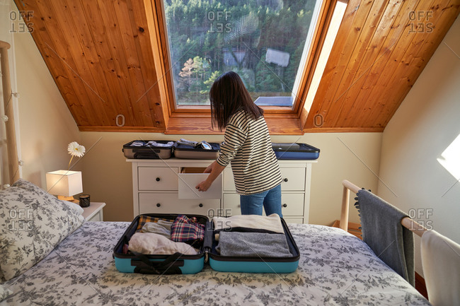 Back view of unrecognizable female taking clothes from dresser while packing suitcases for trip in cozy bedroom at home