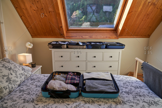 Open luggage with folded clothes placed on bed and dresser in cozy bedroom during journey preparation