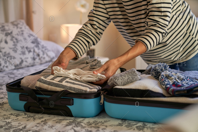 Anonymous lady in casual clothes putting garment into open luggage on bed while preparing for trip at home