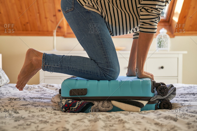 Cropped unrecognizable female pressing and closing packed suitcase on bed while preparing for trip at home
