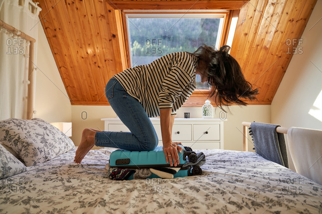 Unrecognizable female pressing and closing packed suitcase on bed while preparing for trip at home
