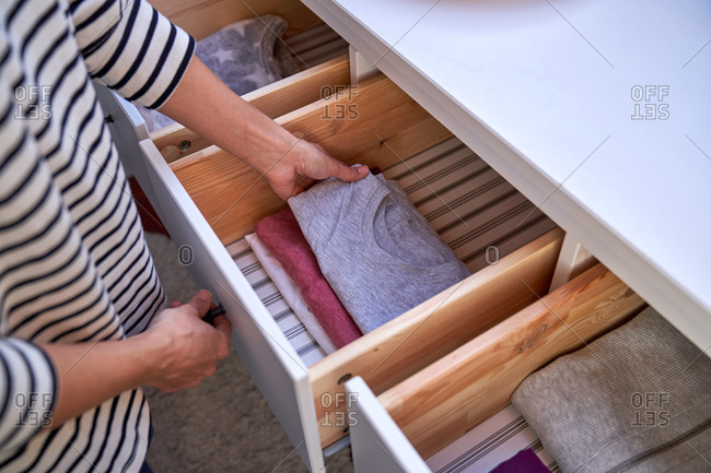 Crop unrecognizable female putting clean t-shirt into open cabinet drawer in cozy room at home