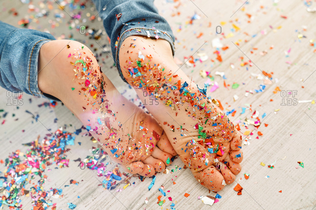 From above of bare feet of faceless child in blue jeans strewing with colorful confetti crawling on floor