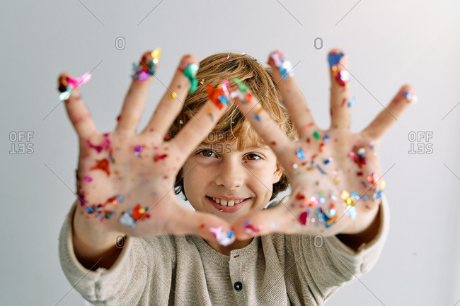 Content boy showing hands in confetti