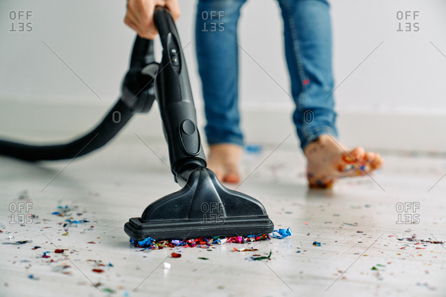 Crop barefoot male in blue jeans using vacuum while cleaning floor from shiny confetti after party