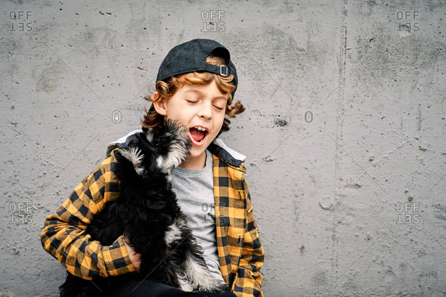Happy boy in checkered shirt and cap sitting with eyes closed next to concrete wall on street and holding Yorkshire Terrier puppy