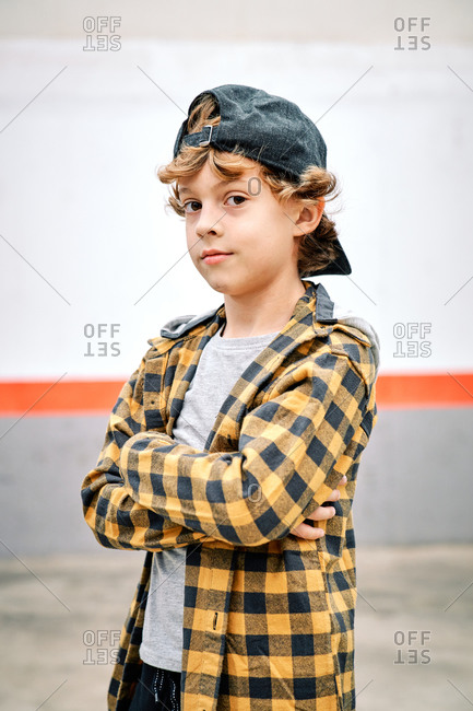 Positive stylish hipster boy in black and yellow checkered shirt and black baseball cap standing with crossed arms  against concrete wall and looking at camera