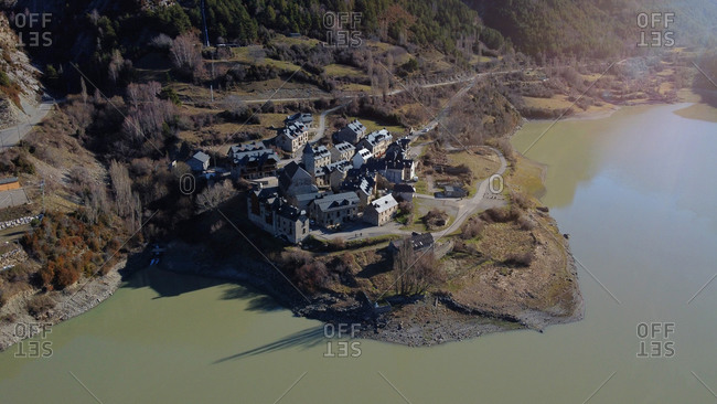 From above houses of small settlement located near slope on snowy mountain and lake against blue sky on sunny day in nature