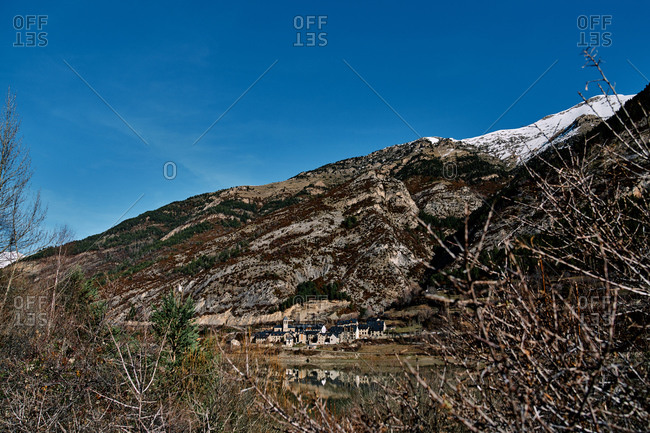 Houses of small settlement located near slope on snowy mountain against blue sky on sunny day in nature