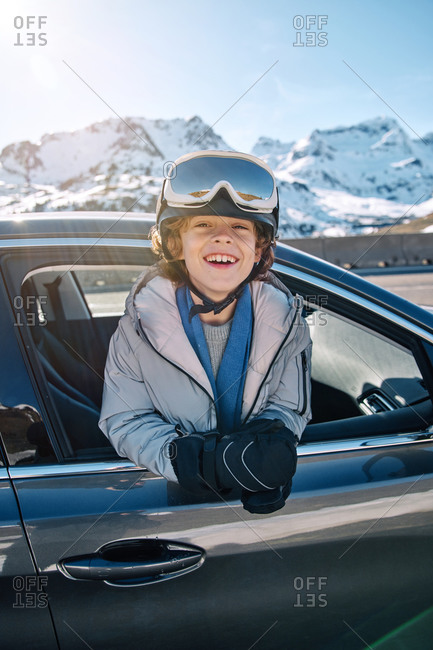Delighted cute boy in helmet with goggles smiling looking at camera while peeking out vehicle window on sunny day on ski resort