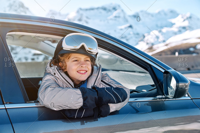 Delighted cute boy in helmet with goggles smiling looking away while peeking out vehicle window on sunny day on ski resort