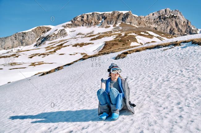 Cute cheerful boy with goggles sitting on snowy ground having fun