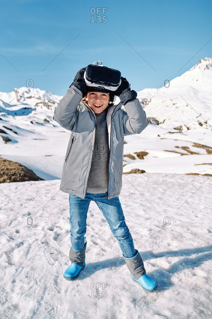 Full body of happy funny boy in outwear standing on snow and exploring virtual reality on sunny winter day in mountains