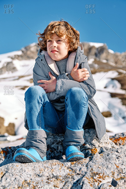 Boy in outwear breathing at cold clasped hands while sitting on blurred background of snowy mountain ridge and cloudless sky in winter countryside