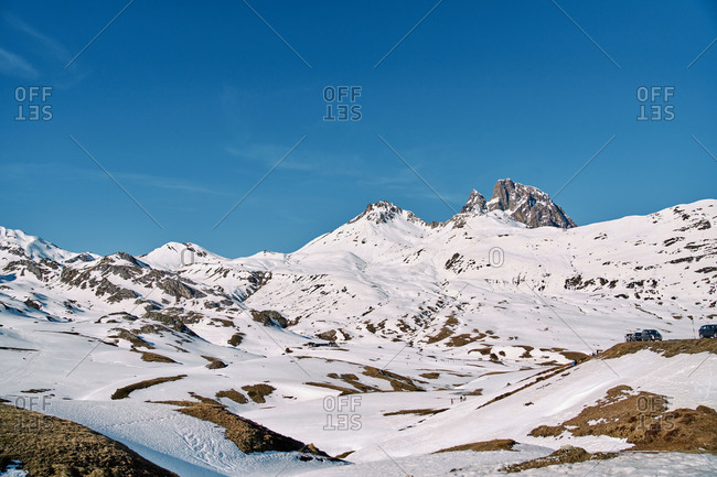 From below mountains covered with white snow located against cloudless blue sky on sunny winter day in nature
