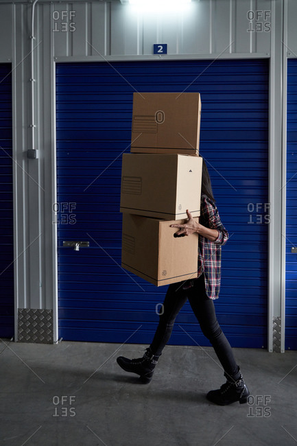 Beautiful brunette woman carrying cardboard boxes in a self storage after making a move