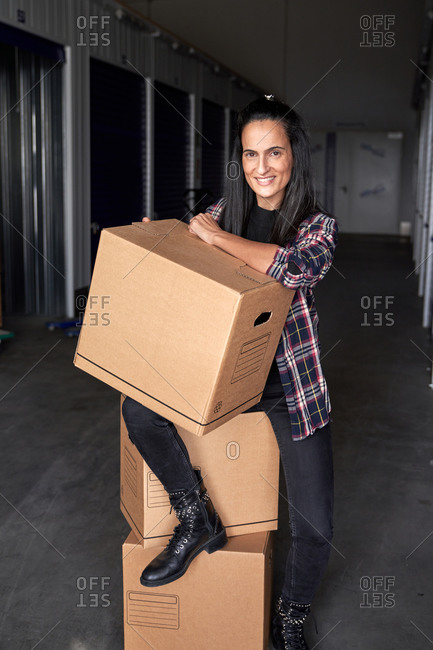 Beautiful woman with moving boxes in a self storage building looking at camera