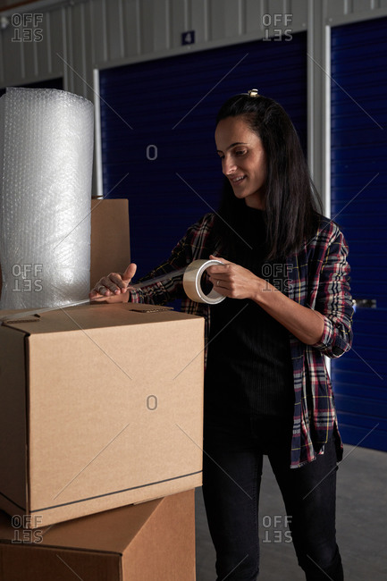 Woman closing moving cardboard boxes with seal tape in a self storage hallway