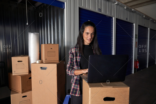 Woman working with a laptop in a moving storage room organizing the boxes in a self storage warehouse