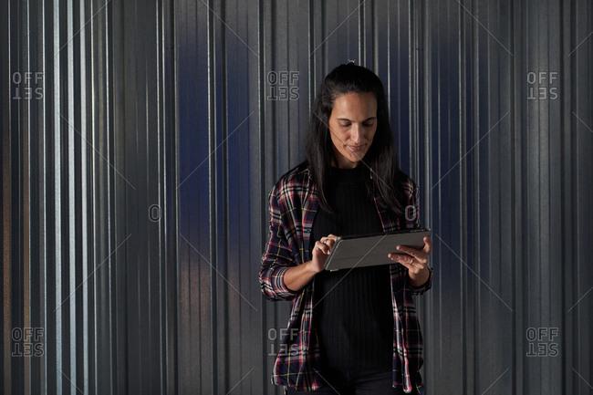Woman standing at self storage door using tablet