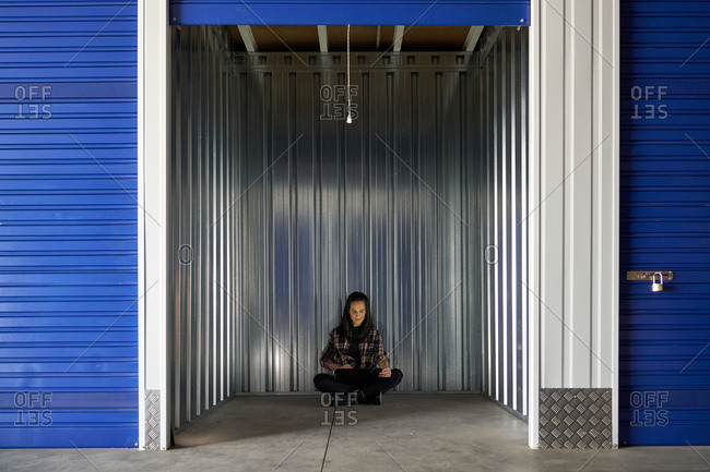 Woman sitting in concrete floor at self storage room in a warehouse using computer