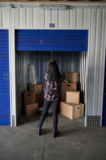 Woman closing or opening self storage door holding tablet