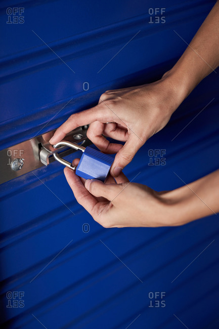 Anonymous cropped woman hands holding a blue padlock while closing it
