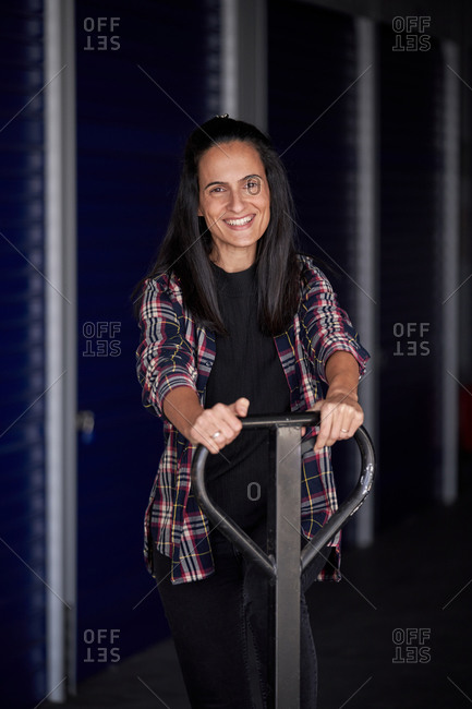 Young woman with moving wheelbarrow organizing her storage room