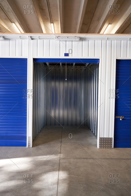 Inside industrial self storage building for rental with blue locked doors