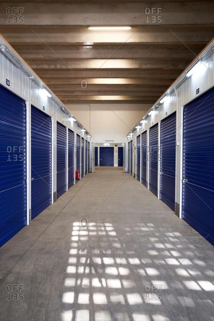 Inside industrial self storage building for rental with blue locked doors