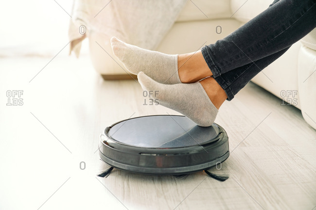 Side view of crop female in jeans and socks sitting on white sofa in room with laminate floor and putting feet on robotic vacuum cleaner