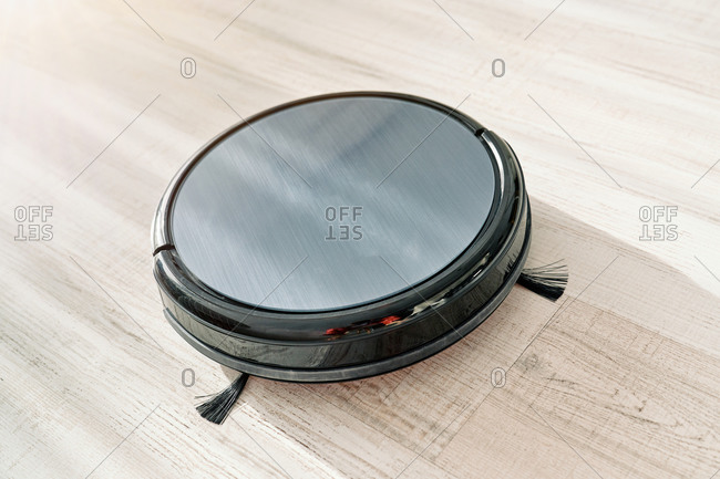 From above of round robotic vacuum cleaner sliding on light laminate floor