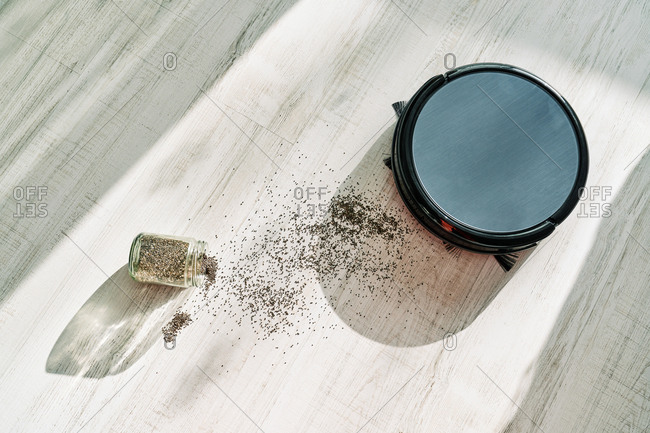 From above of round robotic vacuum cleaner sliding on light laminate floor and removing dirt spilled out of glass pot