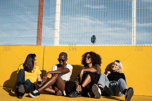 Carefree youthful diverse women in casual clothes laughing and having friendly conversation while sitting in sport playground