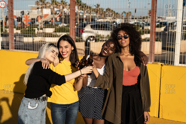 Happy relaxed multiracial charming women in casual clothes clinking glasses and hugging while drinking beer and standing in sunlight on stadium