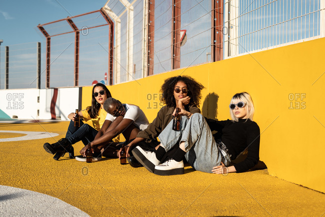Focused young diverse women in trendy clothes and sunglasses looking at camera while sitting during friendly meeting on stadium